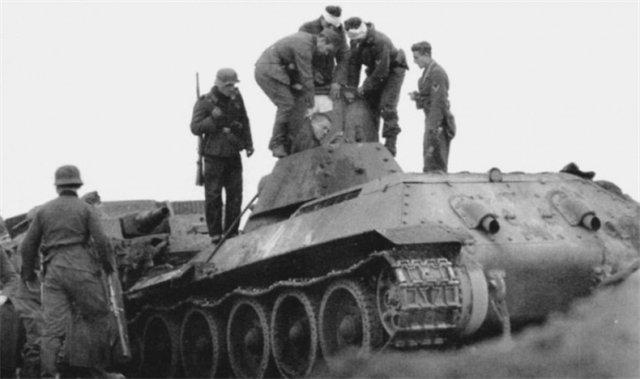 Танк с бортовым номером 4 после лобового столкновения с самоходной установкой. Немецкие солдаты вытаскивают раненого командира танка.